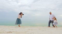 Family photo shoot. Mom takes pictures dad and daughter on the beach Stock Footage