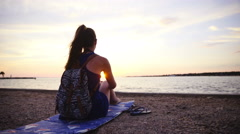Woman on vacation sitting on beach observing beautiful sunset over sea 4K Stock Footage