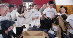 "Group of charity workers wearing t.shirts with the word ""volunteer"" Stock Footage"