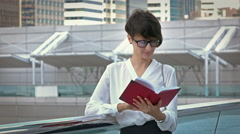 Business and education concept - woman reading book in college or office Stock Footage