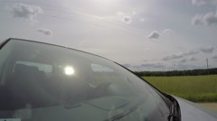 4K. Front View of Man Driving Car on Country Road under Sun Stock Footage