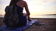 Woman sit on underlay at beach with flipflops beside 4K Stock Footage