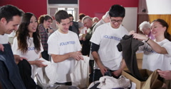 """Group of charity workers wearing t.shirts with the word """"volunteer"""" Stock Footage"""