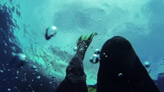 Diver swim underwater in flippers. Many bubbles. Blue clean ocean. Wetsuit Stock Footage