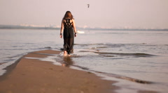 Young woman walking on a coast line water line legs Stock Footage