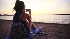 Dolly slide around person at beach take photo of sunset 4K Stock Footage