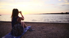 Camera zoom in woman take photo of seascape sunset 4K Stock Footage