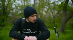 Tired Guy Is Resting On Grass With A Bike Stock Footage