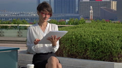 Business woman reading the papers and drinking coffee in the business district Stock Footage