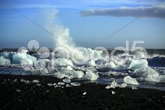 Waves breaking up the icebergs Stock Photos