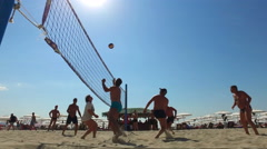 Group young Friends Playing Volleyball On Beach under hot sun shine Stock Footage