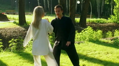 Training in a park. Workout. Young woman and man practicing qigong. Slow motion Stock Footage