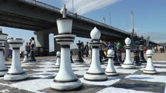 Holiday Murmansk mile. Huge chess on the sand under the bridge. Stock Footage
