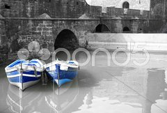 Black and white harbour with two blue boats Stock Photos