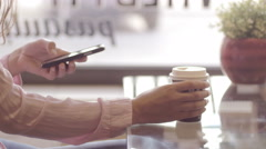 Lady sipping coffee and putting her phone on the table Stock Footage