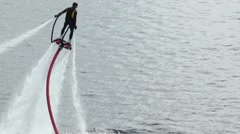 The person on the flyboard flying over dark blue water with sun reflections. Stock Footage