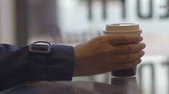 Close-up of girl's hand holding a takeaway coffee in cafe Stock Footage