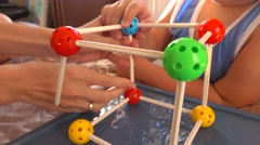 Little boy and his mum playing with colorful plastic construction set. Molecule Stock Footage