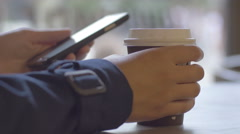 Close-up of girl drinking coffe and using phone against the window in cafe Stock Footage