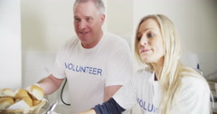 Friendly and attractive voluntary workers standing at a soup kitchen Stock Footage