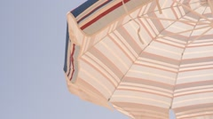 A sun lounger parasol against a clear blue sky Stock Footage