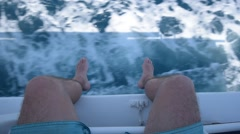 A man Hangs his legs over the side of a moving boat POV Stock Footage