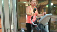 Woman trains on stepper machine in gym. Concept of health and fitness. Stock Footage