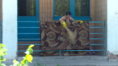 Woman Cleaning Brown Carpet in Yellow Glaves on the Bulcony Outside the House. Stock Footage