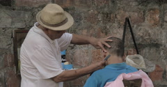 Senior street Barber cuts a man with a straight razor, while a man looks in the Stock Footage
