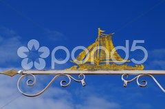 Eisenschild mit Segelschiff vor blauem Himmel Stock Photos