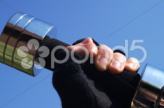 Hand mit Trainingshandschuh und Hantel Stock Photos