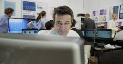 Two mature male financial traders are working in a busy office Stock Footage