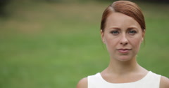 Caucasian woman in a park serious face portrait Stock Footage