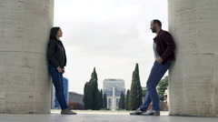 Offended couple standing near columns in city Stock Footage