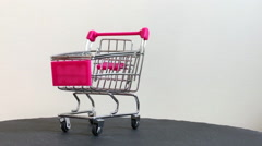 Mini metallic shopping cart turning around Stock Footage
