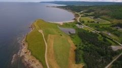 Aerial shot of a field and rocky ocean coast in Cape Breton Stock Footage