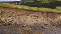 Aerial shot of a mother and baby walking along rugged ocean coast Stock Footage