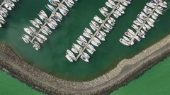Horizontal flight over turquoise water looking straight down on moored boats Stock Footage