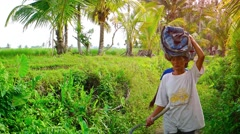 Local laborers carrying cargos on their heads on a Balinese farm. Video 4k Stock Footage