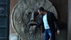 Happy man standing by the Mouth of Truth in Rome, Italy, super slow motion 240fp Stock Footage
