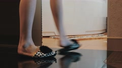 View of young woman in funny slippers walk to bathroom and sit down on bath Stock Footage