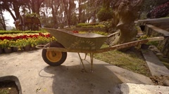 Wheelbarrow sits on the sidewalk at Flower Garden Park in Dalat, Vietnam Stock Footage