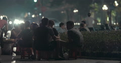 Group of young guys are sitting and speaking at night outdoor Stock Footage