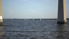 SLOW MOTION PAN OF SAILBOATS UNDER VERY TALL BRIDGE CHESAPEAKE BAY Stock Footage