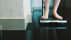 Woman walk on floor stand up on modern scales in apartment. Weighing. Kilograms Stock Footage