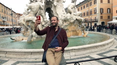 Man taking selfie photo by Fountain of the Four Rivers in Rome, Italy, slow moti Stock Footage