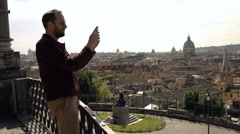 Man taking photo of Italian cityscape with cellphone standing on terrace in Rome Stock Footage