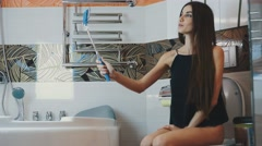 Attractive young girl sitting on toilet in bathroom and take selfie on monopod Stock Footage