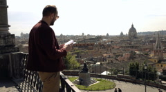 Man reading guide book and admire Italian cityscape on terrace in Rome, Italy Stock Footage