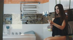 Attractive girl sit on toilet posing for selfie on smartphone. Monopod. Bathroom Stock Footage